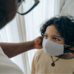 Child getting mask adjusted by an adult.