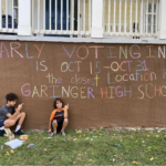 Two kids sitting in front of their chalk drawing promoting early voting.