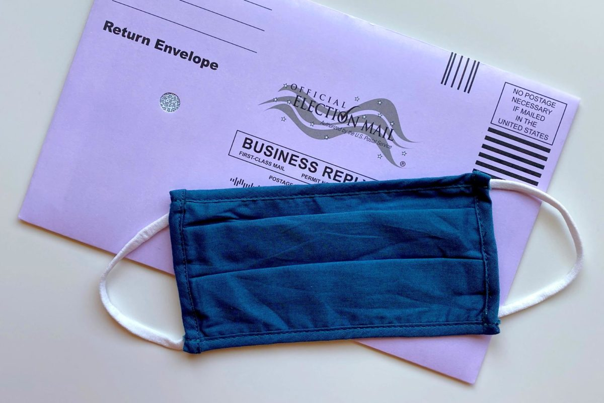 Cloth facemask in front of a mail-in ballot.