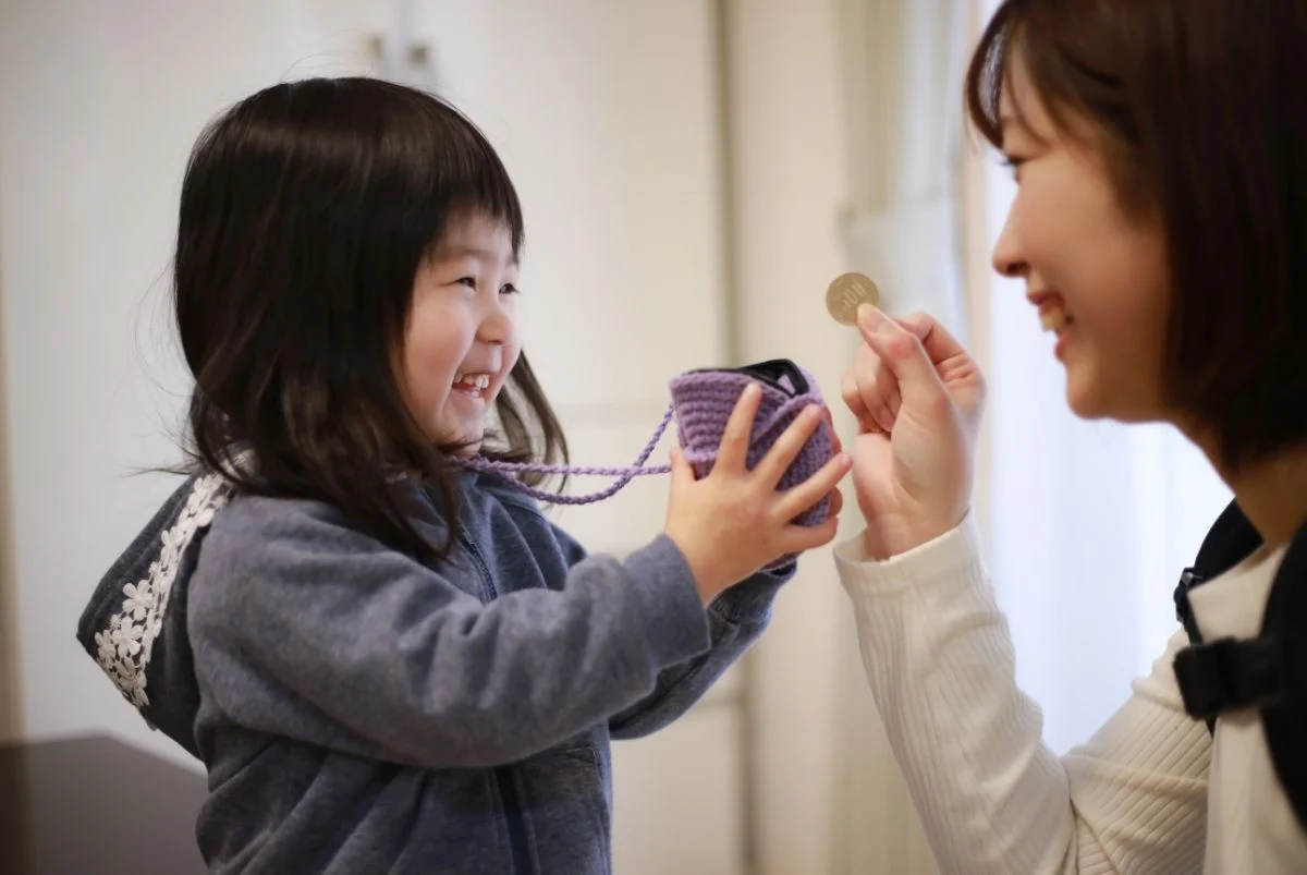 A young girl smiles and holds up a small purple pouch at a smiling woman holding a coin.